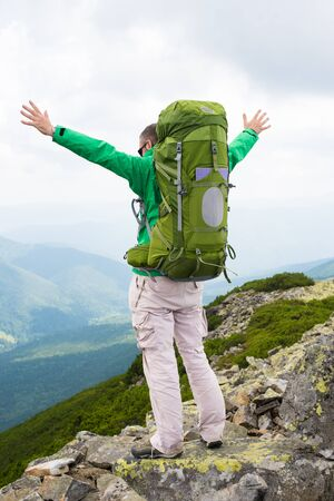 Hiker with backpack standing on top of a mountain . Happy hiker winning reaching life goal, success, freedom and happiness, achievement in mountains. Stock Photo