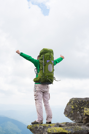 thumbsup: Hiker with backpack standing on top of a mountain . Happy hiker winning reaching life goal, success, freedom and happiness, achievement in mountains. Thumbs-up.