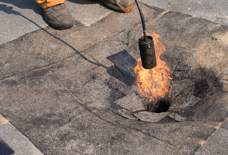 bitumen felt: Roofer doing repair  roof drain. Flat roof installation. Heating and melting bitumen roofing felt. Flat roof repairing with roofing felt. Professional master , making waterproofing