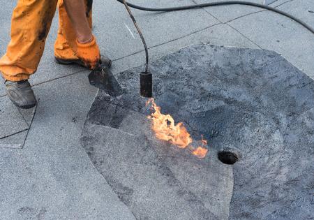 tar felt: Roofer doing repair  roof drain. Flat roof installation. Heating and melting bitumen roofing felt. Flat roof repairing with roofing felt. Professional master , making waterproofing.