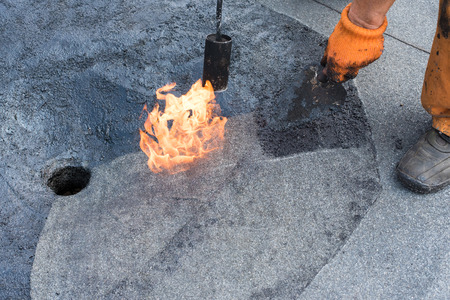 flat roof: Roofer doing repair  roof drain. Flat roof installation. Heating and melting bitumen roofing felt. Flat roof repairing with roofing felt. Professional master , making waterproofing.