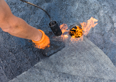 warms: Roofer warms up and brushes shale coating to enhance adhesion when gluing roll material  together. Roofer doing repair  roof drain. Flat roof installation.
