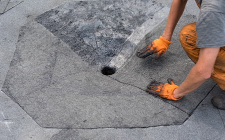 tar felt: Roofer presses, just weld segment rolled waterproofing.  Roofer doing repair  roof drain. Flat roof installation. Heating and melting bitumen roofing felt. Flat roof repairing with roofing felt.