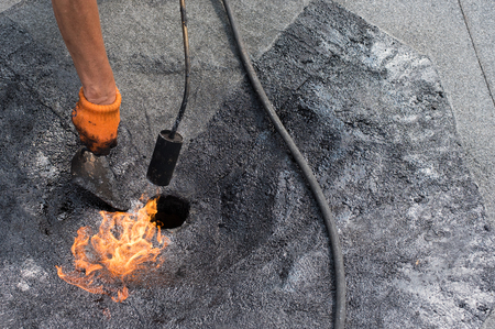 tar felt: Roofer warms up and brushes shale coating to enhance adhesion when gluing roll material  together. Roofer doing repair  roof drain. Flat roof installation.