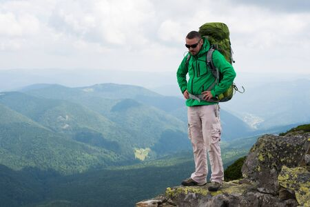 Happy hiker winning reaching life goal, success, freedom and happiness, achievement in mountains.  Hiker  with backpack on top of a mountain.