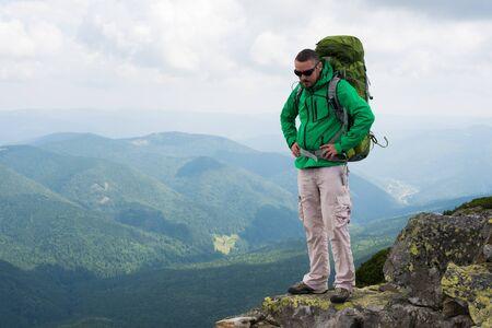 幸せなハイカーが人生の到達目標、成功、自由、幸福、山で成果を獲得します。 山の上にバックパックでハイカー。 写真素材