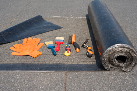 Roll waterproofing, brush, wire brush, trowel, knife gloves. Tool for waterproofing on a background of flat roof.