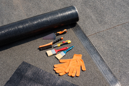 Roll waterproofing, brush, wire brush, trowel, knife, gloves. Tool for waterproofing on a background of flat roof.