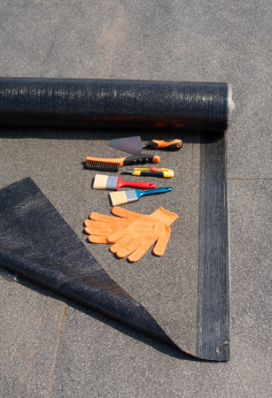 roofing membrane: Roll waterproofing, brush, wire brush, trowel, knife, gloves. Tool for waterproofing on a background of flat roof.