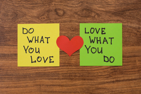 bisiness: Yellow and green note paper with red heart on rustic wooden background. Love What You Do and Do What You Love notes pasted on blackboard.