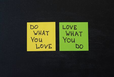 bisiness: Yellow and green note paper on black wooden background. Love What You Do and Do What You Love notes pasted on blackboard.