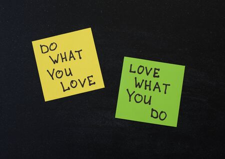 love notes: Yellow and green note paper on black wooden background. Love What You Do and Do What You Love notes pasted on blackboard.
