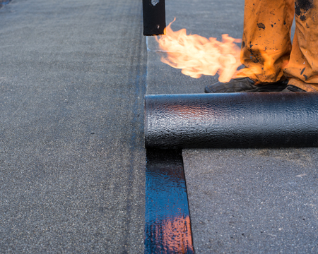 waterproofing material: Roofer man worker at building site installing roll of roofing felt with gas blowpipe torch during construction works. flame during welding of a waterproofing membrane on a roof