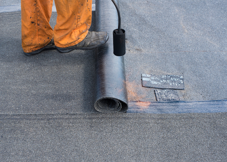 waterproofing material: Professional installation of waterproofing on the concrete foundation. Roofer installing Roofing felt with heating and melting of bitumen roll by torch on flame during roof repair.