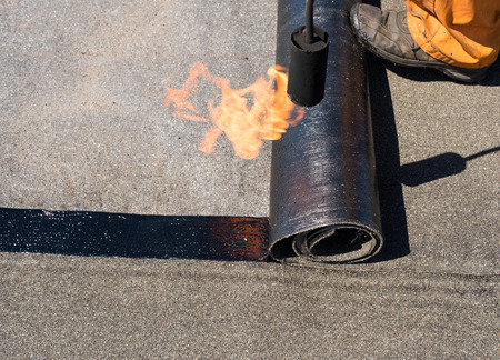 roofing membrane: Roofer man worker at building site installing roll of roofing felt with gas blowpipe torch during construction works. flame during welding of a waterproofing membrane on a roof