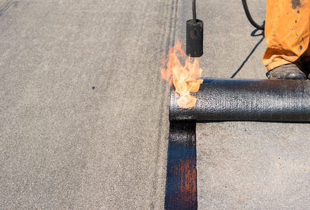 waterproofing material: Professional installation of waterproofing on the concrete foundation. Roofer installing Roofing felt with heating and melting of bitumen roll by torch on flame during roof repair