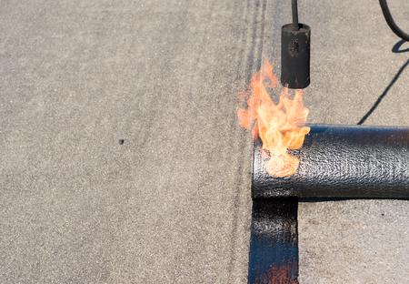 bitumen felt: Professional installation of waterproofing on the concrete foundation. Roofer installing Roofing felt with heating and melting of bitumen roll by torch on flame during roof repair