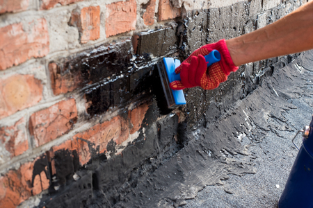 bitumen: Roofer covered brick wall, bitumen primer for improving adhesion during surfacing, contiguity with rolled waterproofing, during the installation of flat roof.