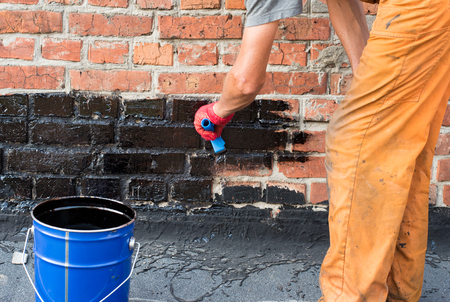 flat roof: Roofer covered brick wall, bitumen primer for improving adhesion during surfacing, contiguity with rolled waterproofing, during the installation of flat roof.