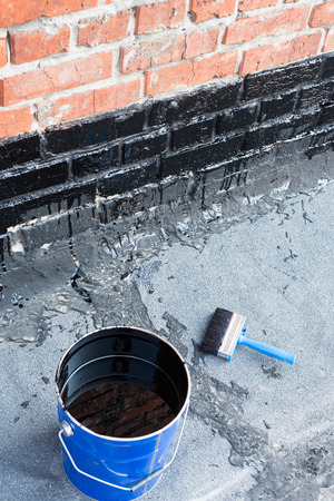 Ceiling brushes  and a bucket of bitumen primer for waterproofing, against the background of a brick wall