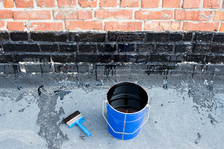bitumen felt: Ceiling brushes  and a bucket of bitumen primer for waterproofing, against the background of a brick wall