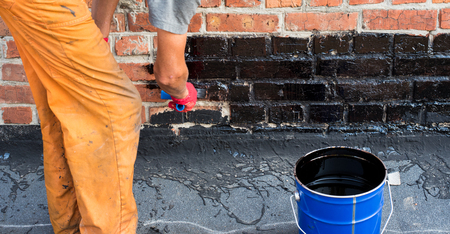 Roofer covered brick wall, bitumen primer for improving adhesion during surfacing, contiguity with rolled waterproofing, during the installation of flat roof.