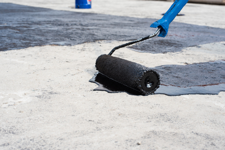 Worker covered surface, bitumen primer for improving adhesion during surfacing,  rolled waterproofing, during the installation of isolation on industrial or household objects