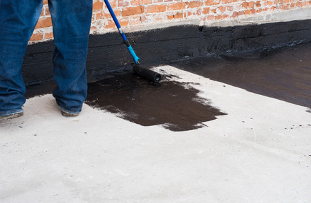 Worker covered surface, bitumen primer for improving adhesion during surfacing,  rolled waterproofing, during the installation of isolation on industrial or household objects Фото со стока - 64476273