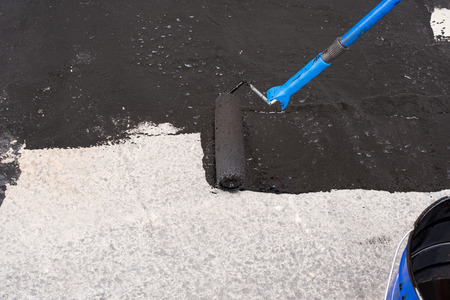 ruberoid: Roller brush. Worker covered surface, bitumen primer for improving adhesion during surfacing,  rolled waterproofing, during the installation of isolation on industrial or household objects