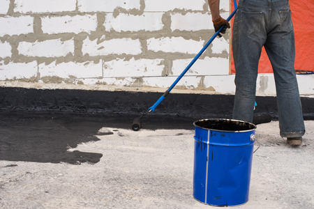 roofing membrane: Worker covered surface, bitumen primer for improving adhesion during surfacing,  rolled waterproofing, during the installation of isolation on industrial or household objects