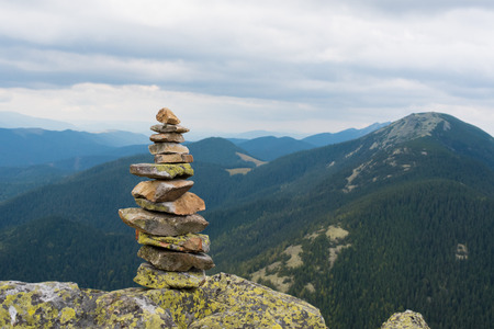Stack of stones  covered with moss on top of the mountain on a background of mountains covered with forests. Concept of balance and harmony. Stack of zen stones. Teamwork balance concept