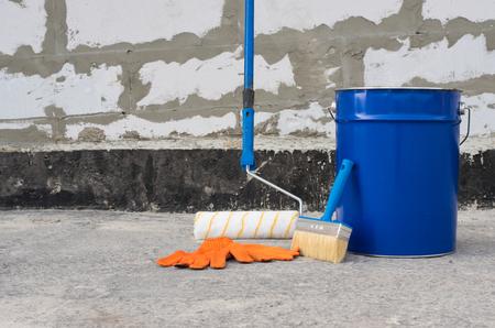 天井ブラシ ブラシとレンガの壁を背景に、防水アスファルト プライマーのバケツ。防水ツール