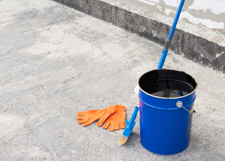 bitumen: Tools for waterproofing. Mittens, roller, ceiling brushes and a bucket of bitumen primer