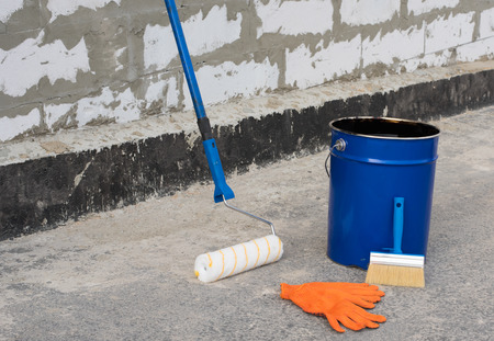 bitumen: Ceiling brushes Brushes and a bucket of bitumen primer for waterproofing, against the background of a brick wall Stock Photo
