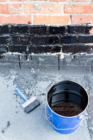 Ceiling brushes Brushes and a bucket of bitumen primer for waterproofing, against the background of a brick wall. Tools for waterproofing. Stock Photo