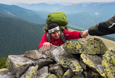 援助の手 - ハイカー男にヘルプの取得ハイキング笑顔幸せな克服する障害物。岩の上の登山者、日没、一人で山の手を与えると上昇に貢献。概念の