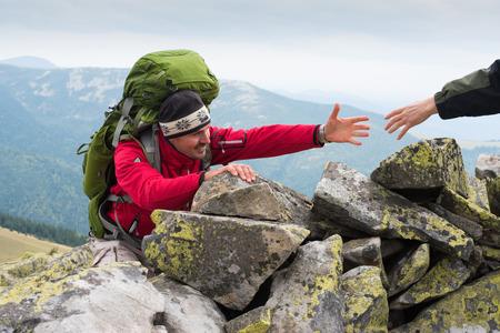 hombre rojo: Mano Amiga en la montaña que recorren alta. Hombres ayudar a otras Caminante al darle la mano. Senderismo temático. instructor de la montaña dio a alguien una mano de ayuda a la cima de la montaña. el trabajo en equipo concepto.