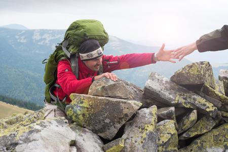 Pomocna dłoń - turystą człowiek coraz pomocy na podwyżkę uśmiechnięte szczęśliwe przezwyciężyć przeszkody. Piesi wspinanie się na skały, góry o zachodzie słońca, jedna z nich podając rękę i pomagając wspinać. Pomoc, wsparcie, pomoc w niebezpiecznej sytuacji. Koncepcja pracy zespołowej.