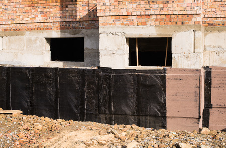 damp proofing: Construction techniques for waterproofing basement and foundations. Insulation material on the basement concrete wall.  House energy saving. Waterproofing house foundation with spray on tar. Stock Photo