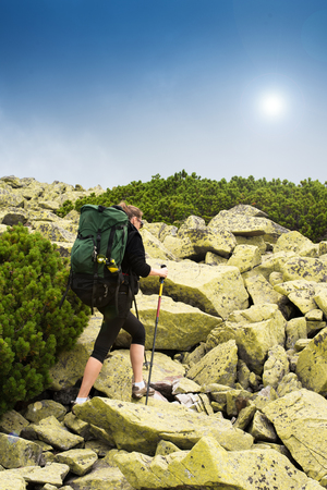 view from behind: Happy young woman traveler climbs the mountain with trekking pole. View from behind