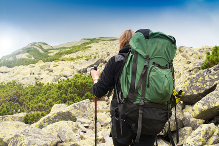 Happy young woman traveler climbs the mountain with trekking pole.View from behind