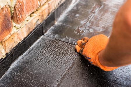屋根葺き職人を押したとき、屋根ふき材料の溶接層だけ。平らな屋根の設置加熱・溶解アスファルト屋根ふきのフェルトします。