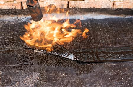 平らな屋根の設置加熱・溶解アスファルト屋根ふきのフェルトします。平らな屋根の屋根ふきのフェルトで修復します。屋根ふきのフェルト。屋根修理。屋根葺き職人の作業します。 屋根葺き職人を作る。屋根葺き職人の作業ツールです。防水 写真素材 - 66828138