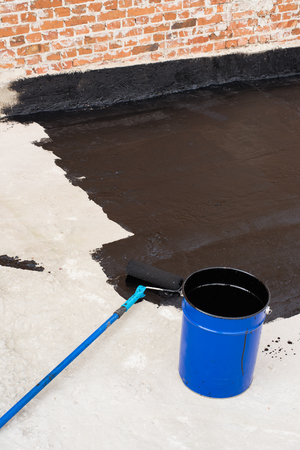 Roller brush. Worker covered surface, bitumen primer for improving adhesion during surfacing, rolled waterproofing, during the installation of isolation on industrial or household objects.
