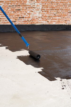 damp proofing:  Roller brush. Worker covered surface, bitumen primer for improving adhesion during surfacing, rolled waterproofing, during the installation of isolation on industrial or household objects. Stock Photo
