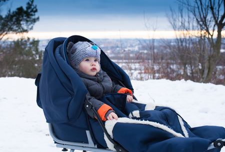 Little boy sitting in a sleigh. Cute little boy sitting on her sledge in winter day. Winter play, snow, sledding - beautiful boy has a fun on snow. Little  boy enjoy a sleigh ride.Outdoor fun for family Christmas vacation. Stock Photo