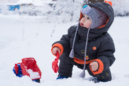 Little boy playing with snow, spade and truck. Baby playing with snow in winter outdoors. Shovel, snow, truck. Winter vacations. Childrens winter games outdoors.