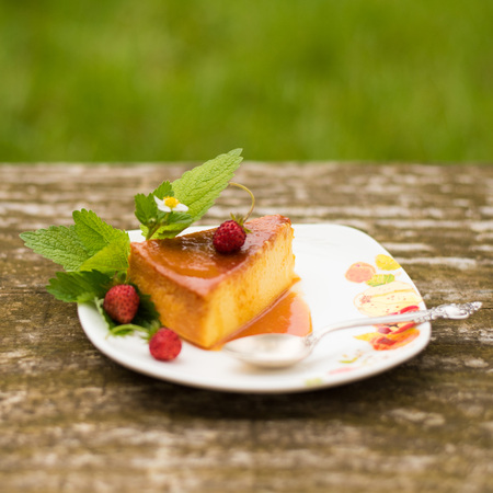 Slice of Milk Pudding with mint and strawberries over a wooden table. Brazilian Flan. French creme caramel dessert or flan with ingredients at the background. Custard pudding Stock Photo