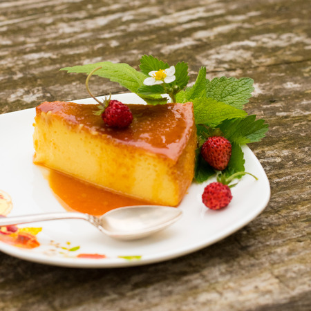 French creme caramel dessert or flan with ingredients at the background, Slice of Milk Pudding with mint and strawberries over a wooden table.Panna cotta dessert with caramel sauce, Custard pudding Stock Photo