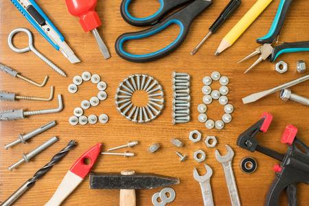 ネジで新年あけましておめでとうございます 2018 組成は、釘、ボルト、ダボ、木製の背景上のツール。新しい年。新年の背景。 写真素材